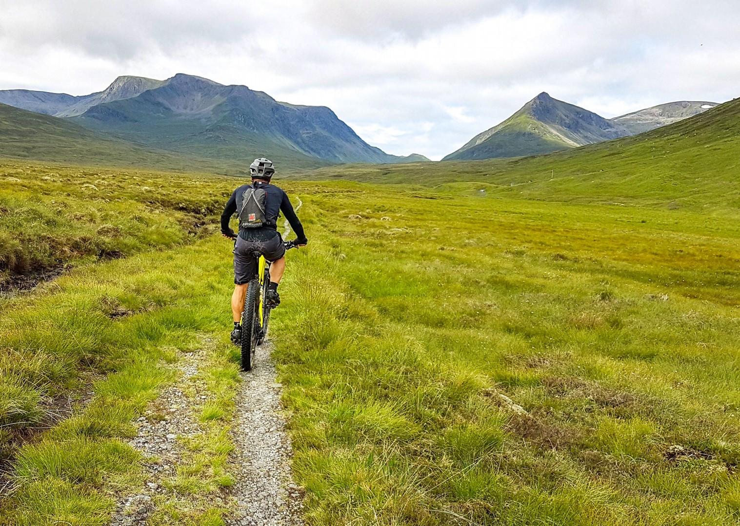 Biciclist pedalând prin peisajul scoțian